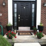 : Black front door with white sidelights looks laconic and stylish