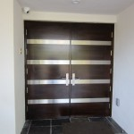 : Double front entry doors are designed for contemporary homes