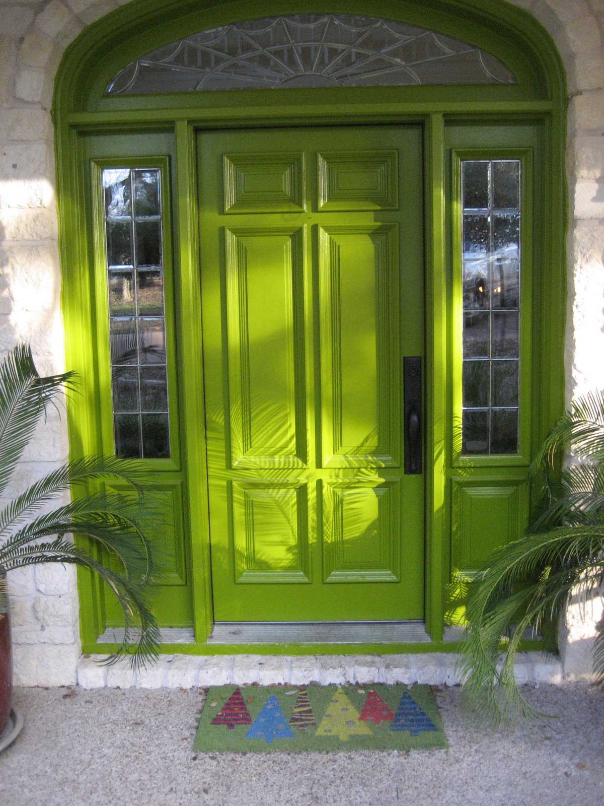 Front door with sidelights of bright colors creates a festive atmosphere