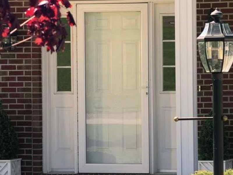 White wood screen door looks stunning when installed in a house with a garden around