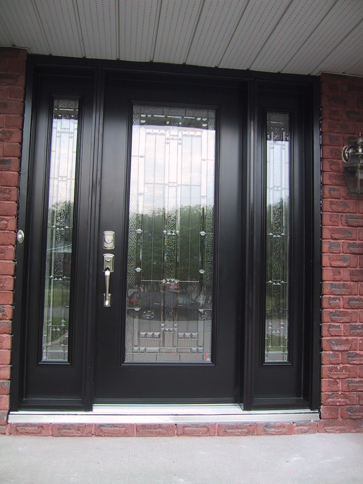 Decorative front doors with sidelights are accomplished with second doors