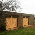 : cedar garage door installation in a stone garage