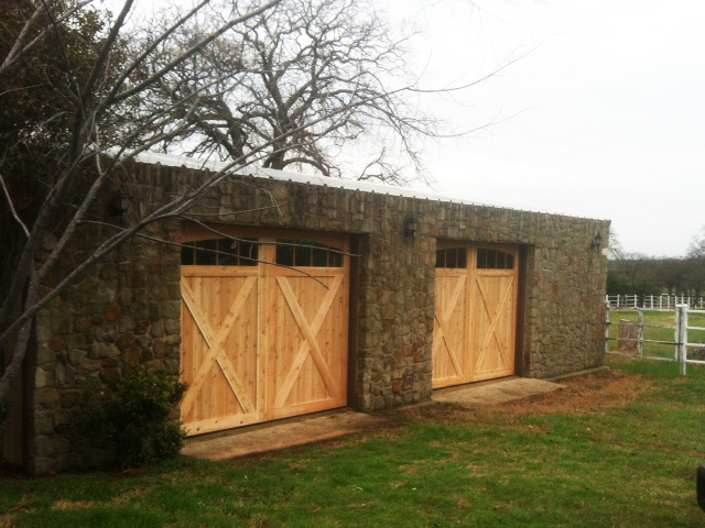 cedar garage door installation in a stone garage