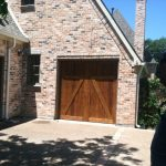 : dark cedar garage door in a home