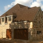 : house with dark cedar garage doors